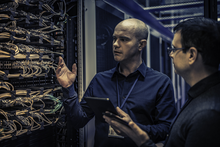 IT technician explaining server configuration to a manager