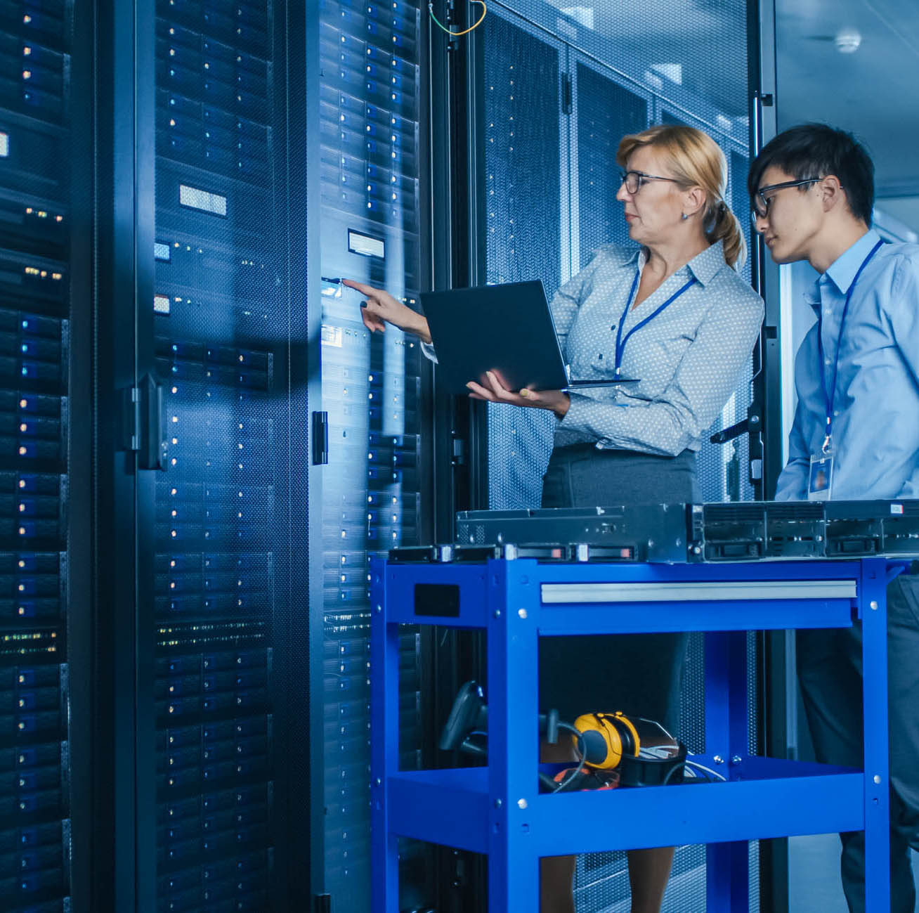 In the Modern Data Center: Engineer and IT Specialist Work with Server Racks, on a Pushcart Equipment for Installing New Hardware. Specialists Doing Maintenance and Diagnostics of the Database.