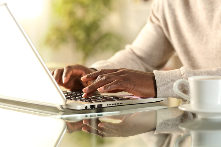 Black man hands typing on a laptop at home
