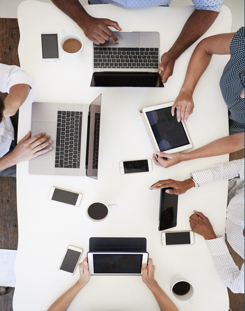 Group working at on computers with phones, overhead shot